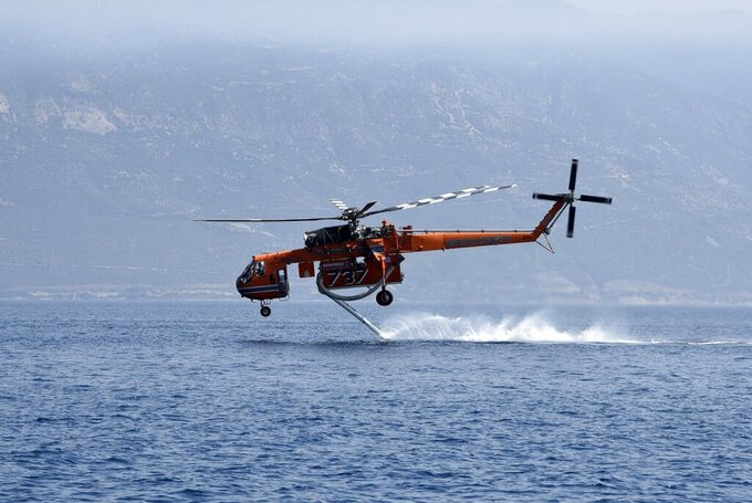 A helicopter fills up with water from the sea near Lampiri village, east of Patras city, Greece, Sunday, Aug. 1, 2021. A wildfire that broke out Saturday in western Greece forced the evacuation of four villages and people on a beach by the Fire Service, the Coast Guard and private boats, authorities said. (AP Photo/Andreas Alexopoulos)