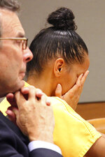 Defense attorney Craig Howard, left, and Gina Virgilio listen to Judge Michael Wolverton in Anchorage, Alaska, on Monday, Oct. 14, 2019, as Wolverton handed down her sentence for murder. Virgilio will serve 60 years in prison for setting fire to the couch on which her boyfriend, Michael Gonzalez, was sleeping in 2012. (AP Photo/Mark Thiessen)
