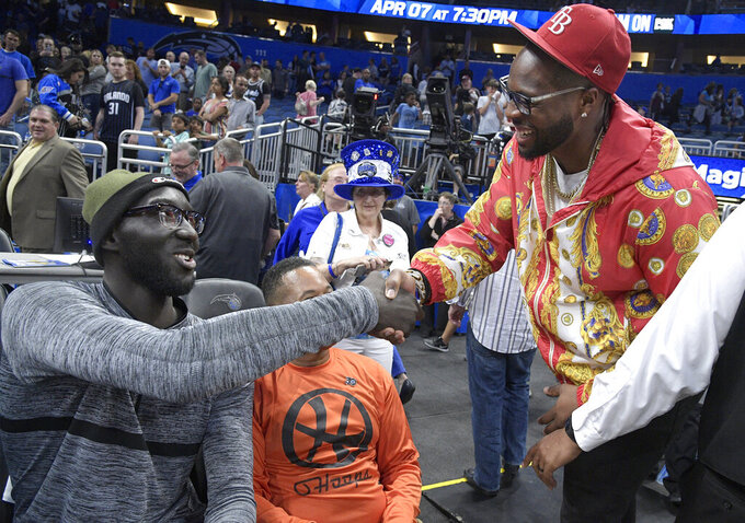 Central Florida center Tacko Fall, left, shakes hands with Tampa Bay Buccaneers defensive tackle Gerald McCoy on the court after an NBA basketball game between the Orlando Magic and Atlanta Hawks, Friday, April 5, 2019, in Orlando, Fla. (AP Photo/Phelan M. Ebenhack)