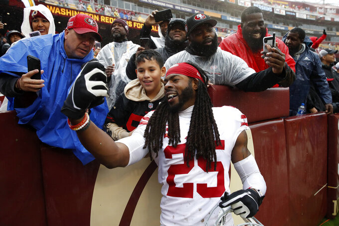 San Francisco 49ers cornerback Richard Sherman takes a photo with a fan after an NFL football game against the Washington Redskins, Sunday, Oct. 20, 2019, in Landover, Md. San Francisco won 9-0. (AP Photo/Alex Brandon)