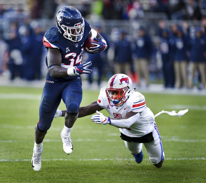 Connecticut running back Kevin Mensah (34) runs the ball in for a touchdown in the fourth quarter of an NCAA college football game against SMU, Saturday, Nov. 10, 2018, in East Hartford, Conn. SMU cornerback Robert Hayes Jr. (7) defends on the play.(AP Photo/Stephen Dunn)