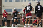 Washington State quarterback Jayden de Laura (4) passes as quarterbacks Jarrett Guarantano (18) and Cammon Cooper (2) look on during the first day of NCAA college football practice, Friday, Aug. 6, 2021, in Pullman, Wash. (AP Photo/Ted S. Warren)