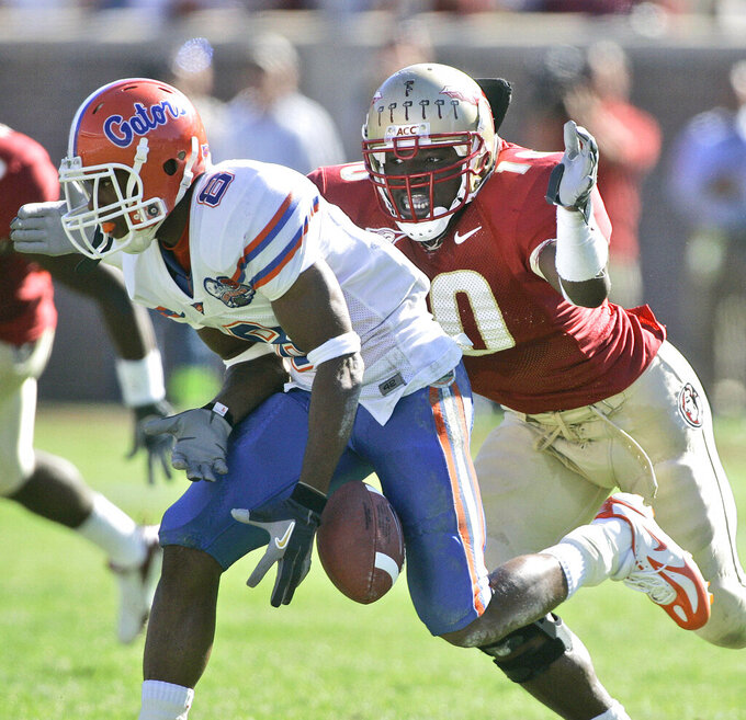 FILE - Florida receiver Percy Harvin, left, drops a second-quarter pass and he is hit by Florida State's Geno Hayes, right, during  an NCAA college football game in Tallahasse, Fla., in this Saturday, Nov. 25, 2006, file photo. Hayes, a former NFL linebacker who starred at Florida State, has died. He was 33. The Tampa Bay Buccaneers on Tuesday, April 27, 2021, confirmed his death. He had liver disease and had been in hospice care. (AP Photo/Phil Coale, File)