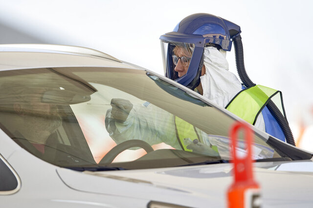 A nurse in protective gear tests for the COVID-19 and coronavirus virus at a drive-thru test location at Bryant Health's LifePointe campus in Lincoln, Neb., Tuesday, March 24, 2020. Testing was by appointment only. (AP Photo/Nati Harnik)