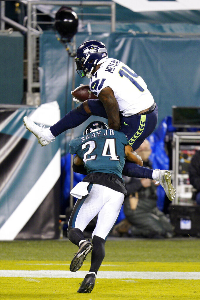 Seattle Seahawks' DK Metcalf (14) tries to hurdle Philadelphia Eagles' Darius Slay (24) during the first half of an NFL football game, Monday, Nov. 30, 2020, in Philadelphia. (AP Photo/Chris Szagola)