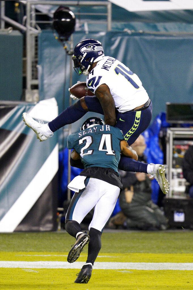 Seattle Seahawks' DK Metcalf (14) tries to hurdle Philadelphia Eagles' Darius Slay (24) during the first half of an NFL football game, Monday, Nov. 30, 2020, in Philadelphia. (AP Photo/Chris Szagola)