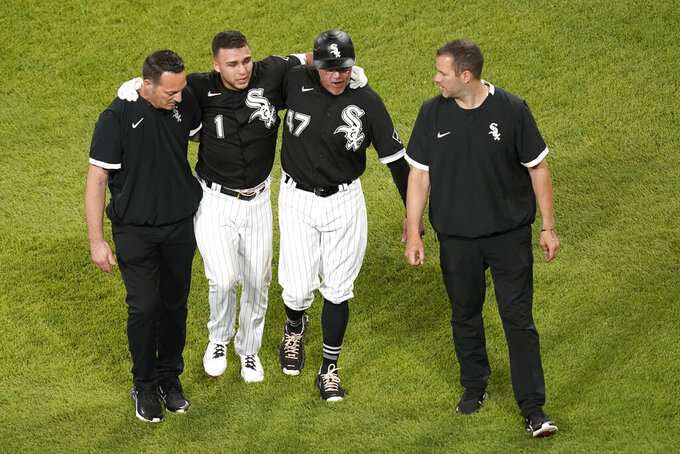 Chicago White Sox's Nick Madrigal (1) favors his right foot as he is helped off the field by third base coach Joe McEwing (47) and members of the medical staff during the seventh inning of the team's baseball game against the Toronto Blue Jays on Wednesday, June 9, 2021, in Chicago. (AP Photo/Charles Rex Arbogast)
