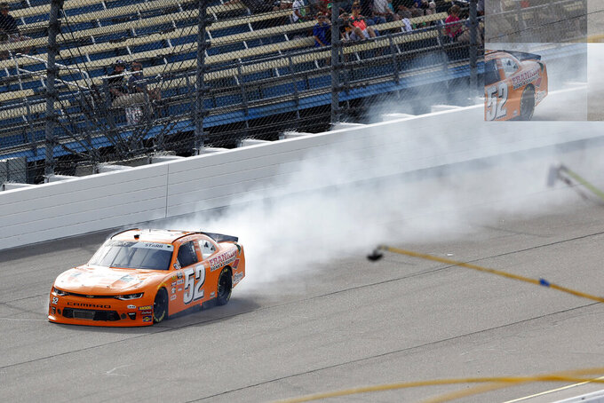 David Starr leaves a trail a smoke as he races his car during a NASCAR Xfinity Series auto race, Sunday, June 16, 2019, at Iowa Speedway in Newton, Iowa. (AP Photo/Charlie Neibergall)