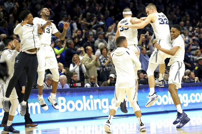 From left to right, Xavier guard Quentin Goodin (3), forward Naji Marshall (13), forward Zach Hankins (35), forward Ryan Welage (32) and guard Elias Harden (4) celebrate their victory after an NCAA college basketball game against Butler, Sunday, Jan. 13, 2019, in Cincinnati. (Kareem Elgazzar/The Cincinnati Enquirer via AP)