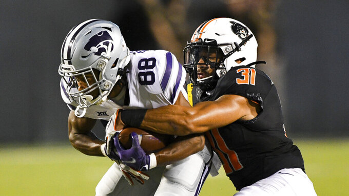 Oklahoma State safety Kolby Harvell-Peel (31) tackles Kansas State wide receiver Phillip Brooks (88) during an NCAA college football game Saturday, Sept. 25, 2021, in Stillwater, Okla.  (AP Photo/Brody Schmidt)