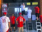 Phandemic Krew members look through a gate during a baseball game between the Philadelphia Phillies and Atlanta Braves in Philadelphia, Monday, Aug. 10, 2020. (AP Photo/Dan Gelston)