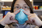 In this photo taken Thursday, Feb. 13, 2020, Public Health — Seattle & King County public health nurse Eileen Benoliel demonstrates how she fits her health care provider mask in her office, in Seattle. Hundreds of people in the United States and thousands around the world are in quarantine at home as authorities try to curb the spread of the virus. (AP Photo/Elaine Thompson)