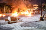 Protesters throw Molotov cocktails towards the forces guarding the Parliament building during protests in Basra, Iraq, Friday, Aug. 21, 2020. Demonstrators burned the outer gate of the entrance to the parliament building in Basra province, the area that produces the lion's share of the crude exporting country's oil. The country's main parliament building is in the capital Baghdad. (AP Photo/Nabil al-Jurani)