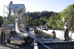 In this photo provided by the California Department of Fish and Wildlife, hatchery workers pump juvenile Chinook salmon into a hatchery truck at the Iron Gate Fish Hatchery in Siskiyou County, Calif. before their relocation on July 7, 2021. Recently California fish and wildlife officials decided not to release more than 1 million hatchery-raised baby chinook salmon into the wild, and instead drove them to several hatcheries that could host them until Klamath River conditions improve. (Travis VanZant/CDFW via AP)