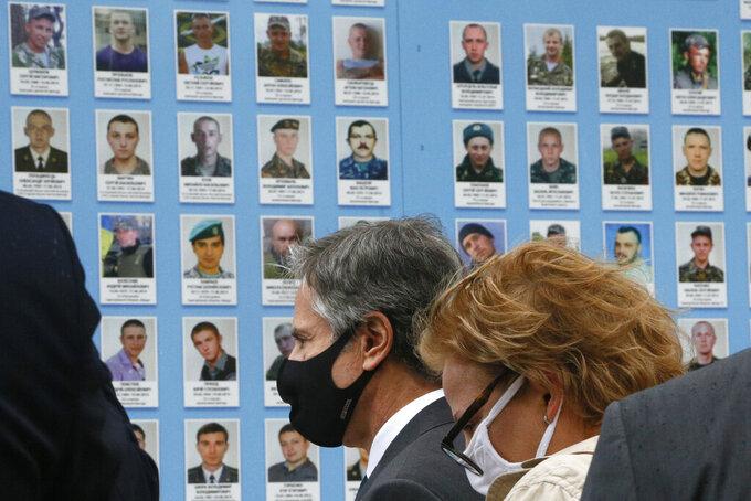 U.S. Secretary of State Antony Blinken pays respect the Memorial Wall of Fallen Defenders of Ukraine in Russian-Ukrainian War in Kyiv, Ukraine, Thursday, May 6, 2021.  (AP Photo/Efrem Lukatsky, Pool)
