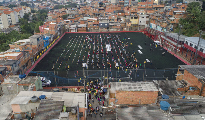"""FILE - In this April 26, 2021 file photo, residents wait on a soccer field for food donated by the local NGO """"G10 Favelas,"""" amid the COVID-19 pandemic in the Capao Redondo area of Sao Paulo, Brazil. In the first quarter of 2021, Brazil saw its highest unemploymentand economic inequality in at least nine years, with the cost of living surging and tent cities and shantytowns emerging. (AP Photo/Andre Penner, File)"""