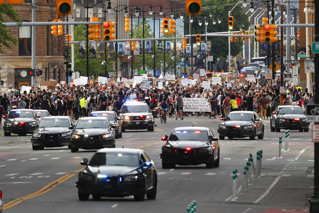 Police lead protesters in a march after a rally in Detroit, Wednesday, June 3, 2020, over the death of George Floyd, an African American man who died on May 25 after a white Minneapolis police officer pressed a knee into his neck for several minutes even after he stopped moving and pleading for air. (AP Photo/Paul Sancya)