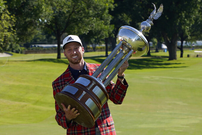 Daniel Berger poses with the championship trophy after winning the Charles Schwab Challenge golf tournament after a playoff round at the Colonial Country Club in Fort Worth, Texas, Sunday, June 14, 2020. (AP Photo/David J. Phillip)