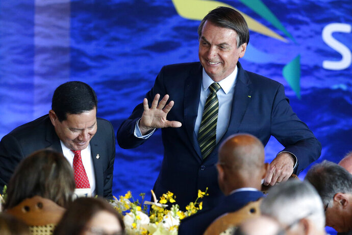Brazil's President Jair Bolsonaro greets attendees during a lunch with Armed Forces General Officers in Brasilia, Brazil, Monday, Dic. 9, 2019. (AP Photo /Eraldo Peres)