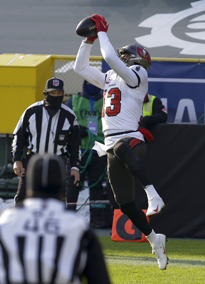 Referees watch as Tampa Bay Buccaneers' Mike Evans grabs a 15-yard touchdown pass against the Green Bay Packers during the first half of the NFC championship NFL football game in Green Bay, Wis., Sunday, Jan. 24, 2021. (AP Photo/Mike Roemer)