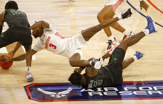 Houston guard DeJon Jarreau (3) dives over Tulane forward Kevin Cross (5) to battle Tulane guard Jaylen Forbes (25) for the ball during the first half of an NCAA college basketball game in the quarterfinal round of the American Athletic Conference men's tournament Friday, March 12, 2021, in Fort Worth, Texas. (AP Photo/Ron Jenkins)