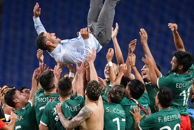 Players of Mexico lift coach Jaime Lozano to celebrate beating 3-1 Japan in the men's bronze medal soccer match at the 2020 Summer Olympics, Friday, Aug. 6, 2021, in Saitama, Japan. (AP Photo/Martin Mejia)