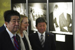 Mary Jean Eisenhower, granddaughter of former U.S. President Dwight D. Eisenhower, center, and Japan's Prime Minister Shinzo Abe, left, watch a photo exposition on the 60th Anniversary commemorative reception of signing of Japan-U.S. Security Treaty at Iikura Guesthouse in Tokyo, Sunday, Jan. 19, 2020. (AP Photo/Eugene Hoshiko, Pool)