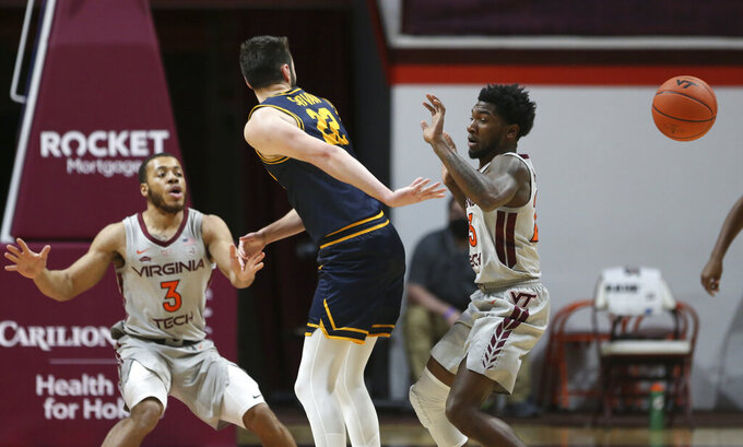 Coppin State's Kenan Sarvan (22) passes behind his back past Virginia Tech's Wabissa Bede (3) and Tyrece Radford during the first half of an NCAA college basketball game, Saturday, Dec. 19, 2020 in Blacksburg, Va. (Matt Gentry/The Roanoke Times via AP, Pool)