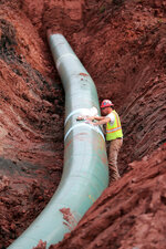 FILE - In this Aug. 21, 2017, file photo, a pipe fitter lays the finishing touches to the replacement of Enbridge Energy's Line 3 crude oil pipeline stretch in Superior, Wisc. Environmental and tribal groups opposed to Enbridge Energy's plan to replace its aging Line 3 crude oil pipeline are planning large scale protests with potential arrests Monday, June 7, 2021, as the Canadian-based company gears up for a final construction push. (Richard Tsong-Taatarii/Star Tribune via AP)