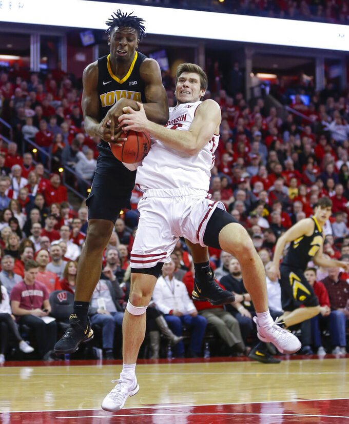 Iowa's Tyler Cook, left, and Wisconsin's Ethan Happ battle for a rebound during the second half of an NCAA college basketball game Thursday, March 7, 2019, in Madison, Wis. Wisconsin won 65-45. (AP Photo/Andy Manis)