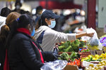 People shop at Queen Victoria Market hours before a citywide curfew is introduced in Melbourne, Sunday, Aug. 2, 2020. The premier of Australia's hard-hit Victoria state has declared a disaster among sweeping new coronavirus restrictions across Melbourne and elsewhere from Sunday night. (Erik Anderson/AAP Image via AP)