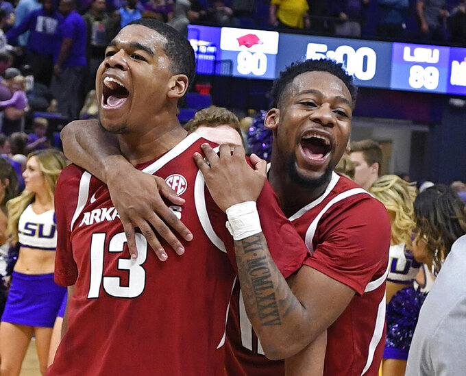 Arkansas guard Mason Jones (13) celebrates with guard Keyshawn Embery-Simpson (11) after an NCAA college basketball game against LSU on Saturday, Feb. 2, 2019, in Baton Rouge, La. Arkansas won 90-89. (AP Photo/Bill Feig)