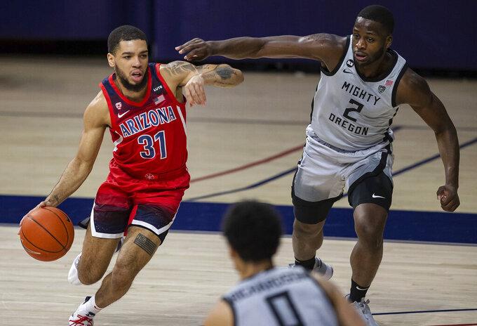 Arizona guard Terrell Brown Jr. (31) dribbles across the court as Oregon forward Eugene Omoruyi (2) defends during an NCAA college basketball game, Saturday, Feb. 13, 2021, in Tucson, Ariz. (Josh Galemore/Arizona Daily Star via AP)