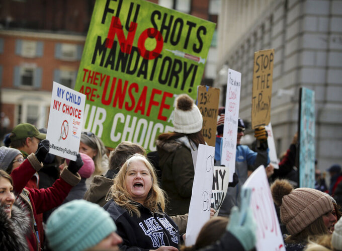 Demonstrators rally outside the Massachusetts State House, protesting Governor Charlie Baker's order for mandatory influenza vaccinations for students in Boston on Wednesday, Jan. 6, 2021.  (Craig F. Walker/The Boston Globe via AP)