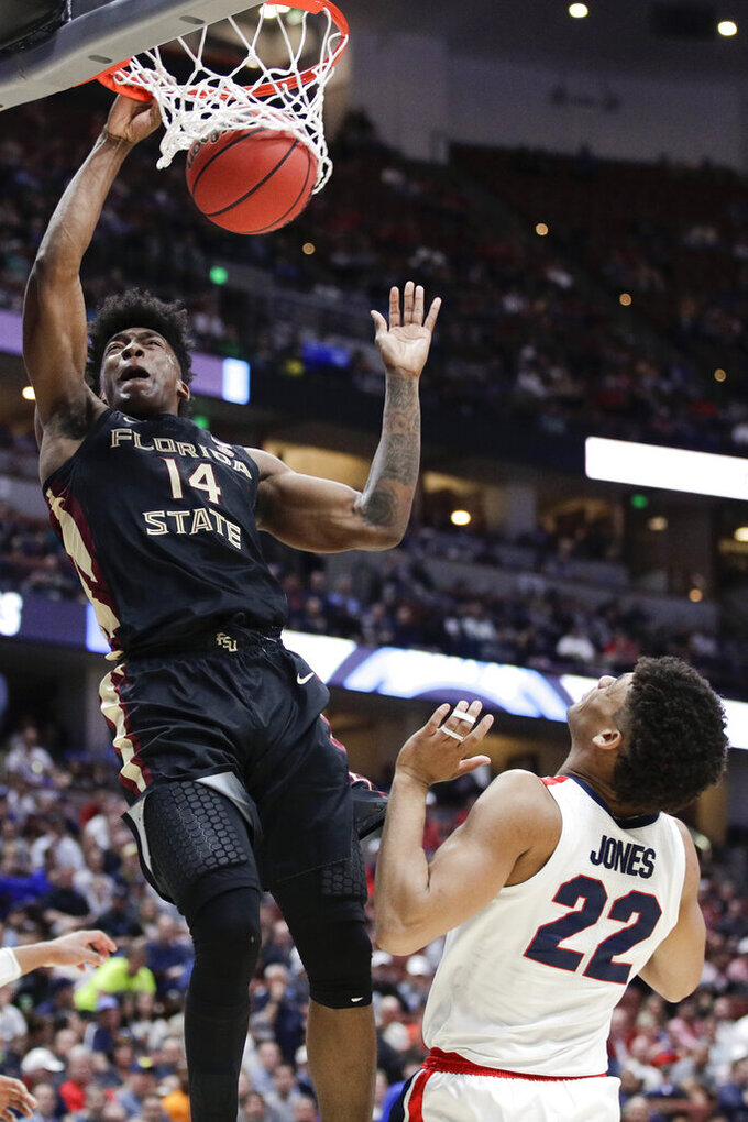 Florida State guard Terance Mann, left, dunks over Gonzaga forward Jeremy Jones during the second half an NCAA men's college basketball tournament West Region semifinal Thursday, March 28, 2019, in Anaheim, Calif. (AP Photo/Jae C. Hong)