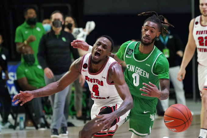 Western Kentucky guard Josh Anderson (4) is fouled by North Texas guard James Reese (0) during the first half of the championship game in the NCAA Conference USA men's basketball tournament Saturday, March 13, 2021, in Frisco, Texas. (AP Photo/Tony Gutierrez)