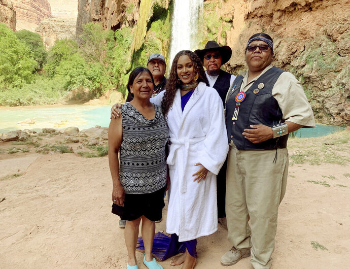 This July 10, 2019 photo provided by Parkwood Entertainment shows from left to right, Havasupai tribal Chairwoman Muriel Uqualla, Councilman Richard Watahomigie, Beyoncé, Councilman Claudius Putesoy and Vice Chairman Matthew Putesoy in Supai, Ariz.  Beyoncé filmed part of her latest music video,