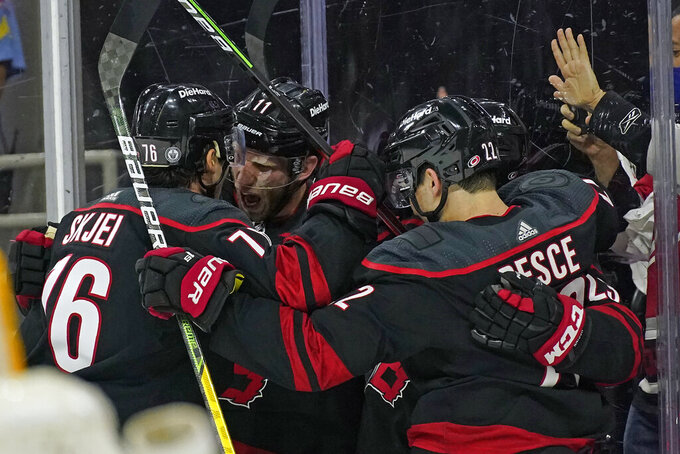 Carolina Hurricanes' Brady Skjei (76) and center Jordan Staal (11) celebrate Staal's goal against the Nashville Predators with defenseman Brett Pesce during the second period in Game 1 of an NHL hockey Stanley Cup first-round playoff series in Raleigh, N.C., Monday, May 17, 2021. (AP Photo/Gerry Broome)