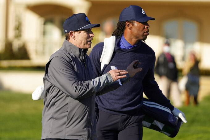 Steve Young, left, looks over the second green with Larry Fitzgerald during the charity challenge event of the AT&T Pebble Beach Pro-Am golf tournament Wednesday, Feb. 10, 2021, in Pebble Beach, Calif. (AP Photo/Eric Risberg)