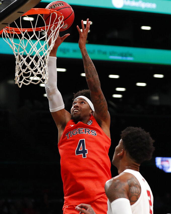 New Mexico guard Vance Jackson (2) watches as Auburn forward Javon Franklin (4) tips the ball into the basket during the second half of an NCAA college basketball game in the Legends Classic, Monday, Nov. 25, 2019, in New York. Auburn defeated New Mexico 84-59. (AP Photo/Kathy Willens)