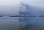 Taal volcano spews ash in view from Batangas, southern Philippines on Monday, Jan. 13, 2020. Red-hot lava gushed out of a volcano near the Philippine capital on Monday, as thousands of people fled the area through heavy ash. Experts warned that the eruption could get worse and plans were being made to evacuate hundreds of thousands. (AP Photo/Gerrard Carreon)
