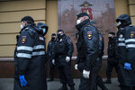 Police prepare to detain protesters during one-man protests in violation of the city's coronavirus restrictions, in front of the city's police headquarters in Moscow, Russia, Friday, May 29, 2020. Sixteen people have been detained in Moscow after holding staggered one-person protests in violation of the city's coronavirus restrictions. The activists were protesting Friday against the arrest of a prominent Russian journalist Ilya Azar, who was sentenced to 15 days in jail the night before, also for holding a one-man protest amid lockdown. (AP Photo/Pavel Golovkin)