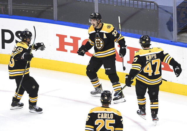 Boston Bruins center Patrice Bergeron (37) reacts with teammates Brad Marchand (63) Torey Krug (47) and Brandon Carlo (25) after scoring the game-winning goal against the Carolina Hurricanes during the second overtime period of an NHL Eastern Conference Stanley Cup playoff game in Toronto on Wednesday, Aug. 12, 2020. (Nathan Denette/The Canadian Press via AP)