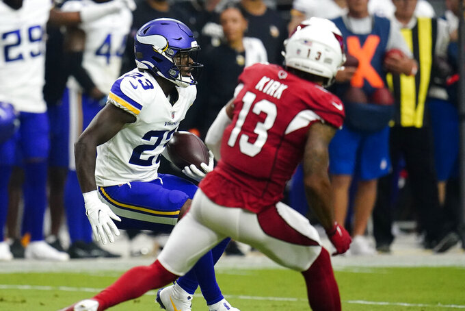 Minnesota Vikings free safety Xavier Woods (23) runs after an interception against the Arizona Cardinals during the second half of an NFL football game, Sunday, Sept. 19, 2021, in Glendale, Ariz. (AP Photo/Ross D. Franklin)