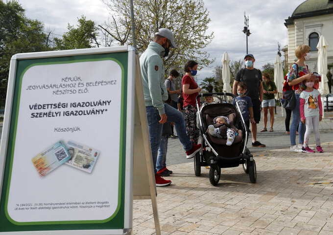 People wait for the Budapest Zoo to reopen in Budapest, Hungary, Saturday, May 1, 2021. Hungary on Saturday loosened several COVID-19 restrictions for people with government-issued immunity cards, the latest in a series of reopening measures that have followed an ambitious vaccination campaign. (AP Photo/Laszlo Balogh)