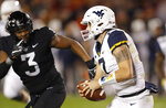 West Virginia quarterback Will Grier, right, runs from Iowa State defensive end JaQuan Bailey (3) during the first half of an NCAA college football game, Saturday, Oct. 13, 2018, in Ames, Iowa. (AP Photo/Charlie Neibergall)