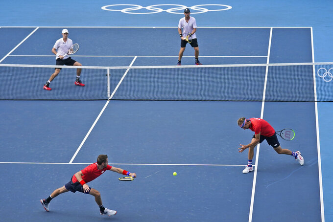 The United States doubles team of Tennys Sandgren, bottom right, and Austin Krajicek, bottom left, try to chase down a ball hit by the New Zealand doubles team of Michael Venus, top right, and Marcus Daniell during the men's doubles bronze medal match of the tennis competition at the 2020 Summer Olympics, Friday, July 30, 2021, in Tokyo, Japan. (AP Photo/Seth Wenig)