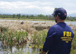 In this May 2016 photo, FBI agents conduct a search in and around a pond for Katherine