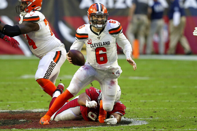 Cleveland Browns quarterback Baker Mayfield (6) escapes the reach of Arizona Cardinals defensive tackle Corey Peters during the second half of an NFL football game, Sunday, Dec. 15, 2019, in Glendale, Ariz. (AP Photo/Ross D. Franklin)