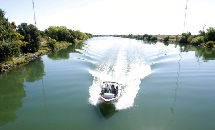 FILE — In this Monday, Sept. 23, 2013 file photo, a boat cruises down the Delta Cross Channel between the Sacramento River and Snodgrass Slough near Walnut Grove, Calif. California officials announced Thursday, Nov. 21, 2019 that they will sue the Trump administration to block its recently announced rules governing water in the San Joaquin Delta. (AP Photo/Rich Pedroncelli, File)